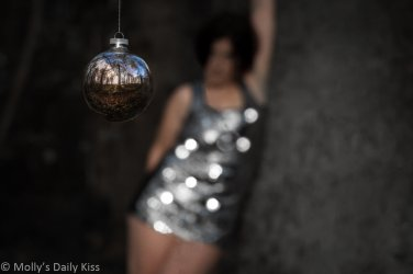 Christmas bauble hanging in the woods with molly is sparkly dress in the background with bokeh sparkles