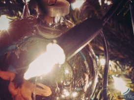 Cropped image of nude molly reflected in christmas bauble