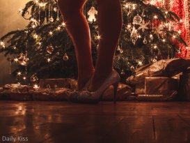 Molly wearing gliter high heels in front of christmas tree with angel decorations shoing between her legs
