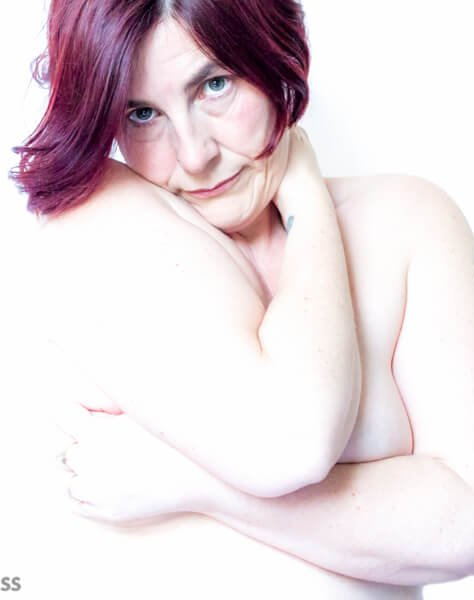 molly naked with purple hair hugging herself and looking into the camera