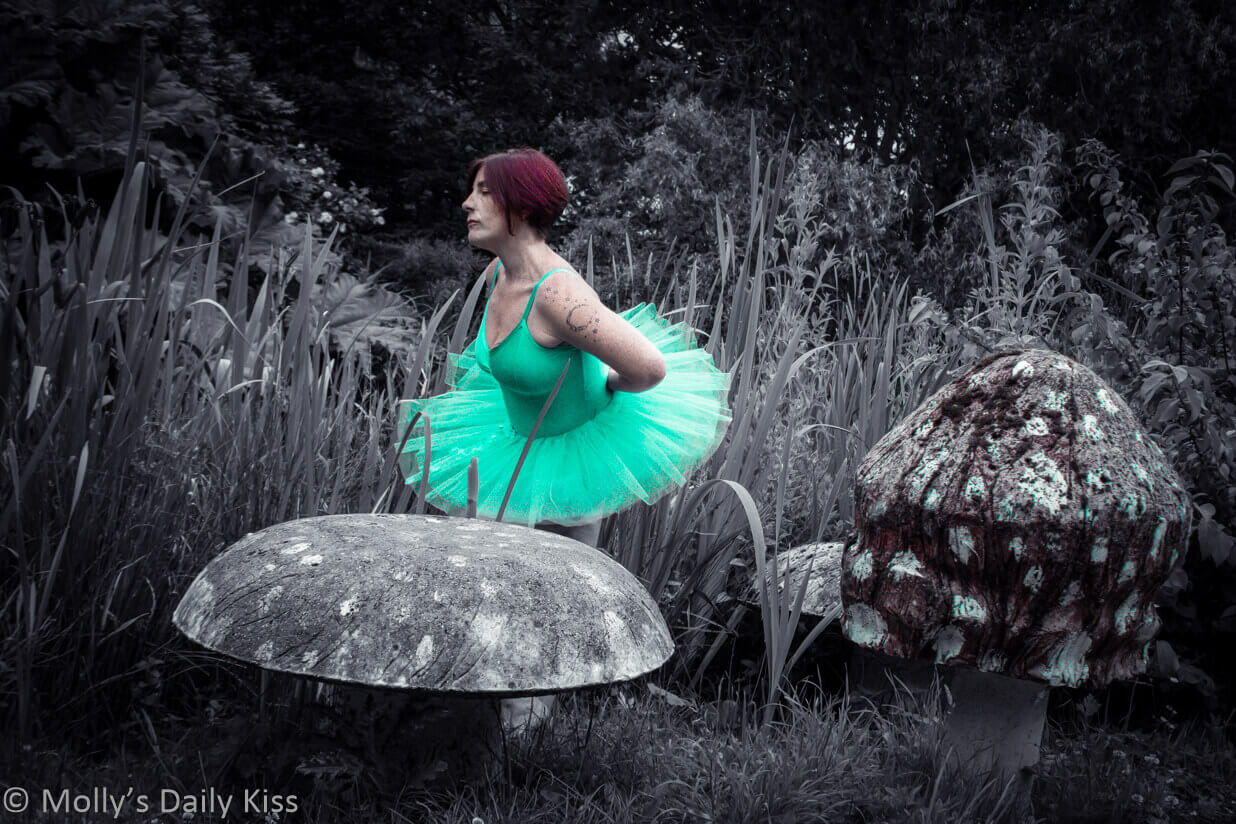 Molly dressed in aqua green fairy tutu with giant stone mushrooms and in a garden setting