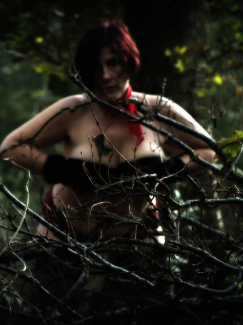 Molly covering her breasts with gloved hands wearing a red scarf behind falled branches in the woods