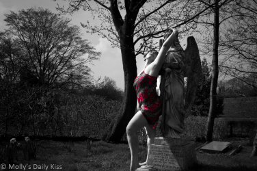 Molly wearing red flower print lingerie and holding onto an angel statue in a graveyard for a post called Sirens