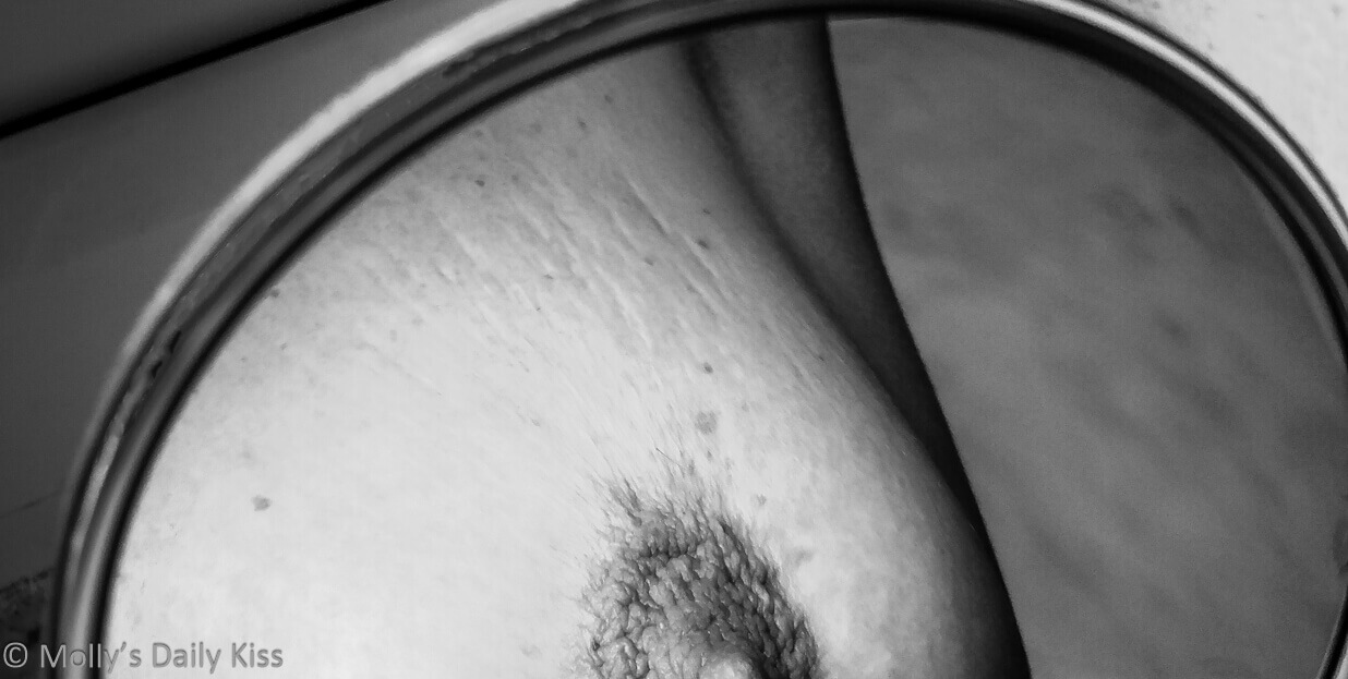 cropped image of molly's breast reflected in small round mirror