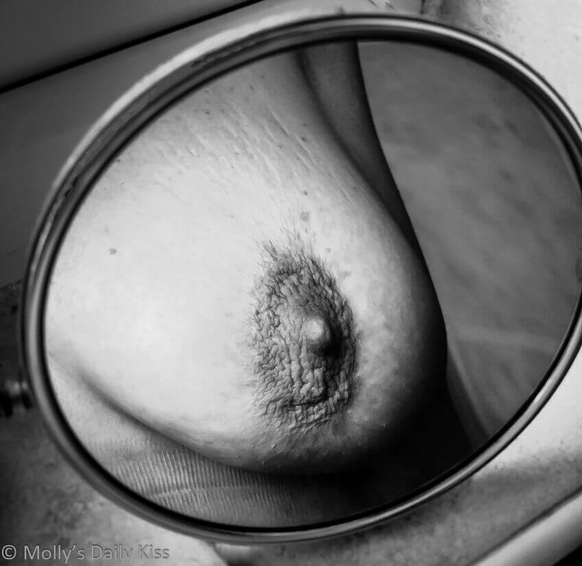 Black and white image of molly's breast in round mirror