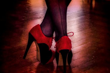 womans legs crossed over standing wearing red and black high heels and seemed stockings