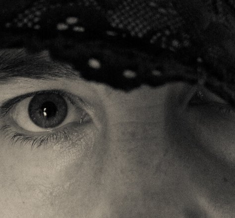 One eye looking into camera the other covered by black lace edited in black and white
