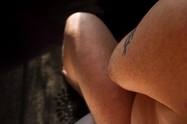 Looking down Michaels arm at his side and leg that is bathed in sunlight
