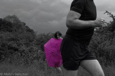 An outtakes image of Molly behind umbrella with man running through the shot