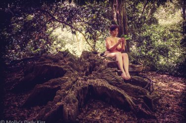 Molly nude sitting on giant tree stump with book made of leaves