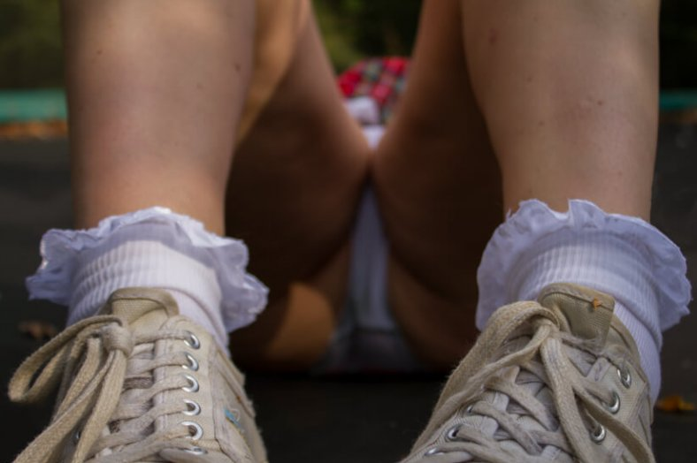 Molly wearing sneakers and school girl frilly sock looking uo through her legs to white panties