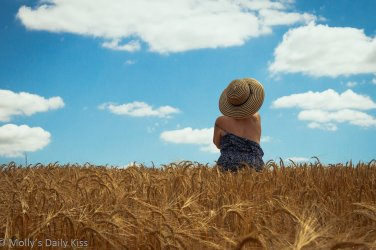 Molly wearing big summer hat standing in field of wheat with her dress slipping down