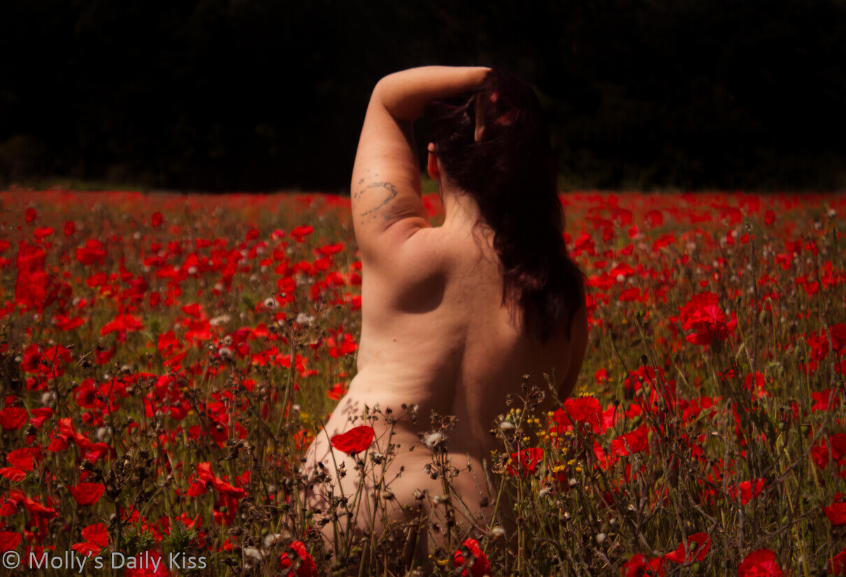 Molly standing naked with her back to the camera in a field of red poppies