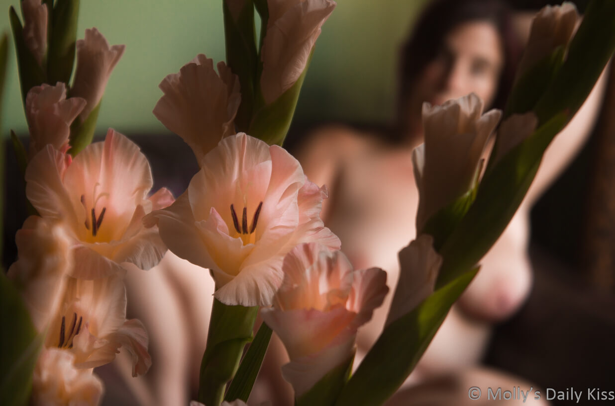 Molly sitting naked behind pink gladioli