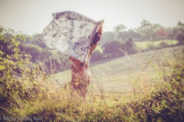 Molly standing in undergrowth holding a scarf up that is blowing in the wind for post called she's like the wind