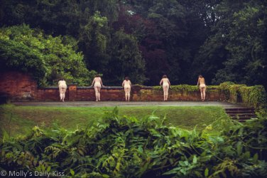5 naked women learning over a wall in a lush green garden