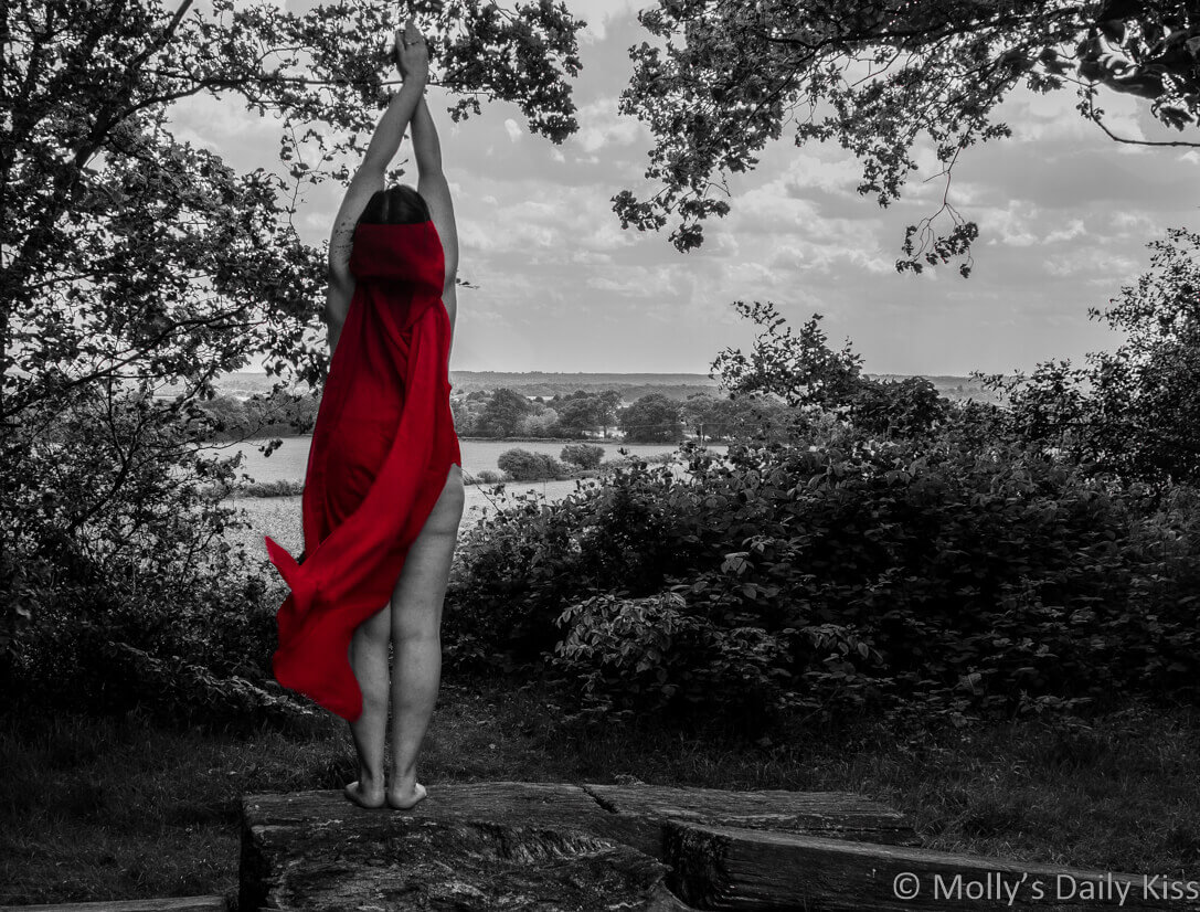 molly reaching up into the sky wearing red cape over looking fields which are edited into black and white
