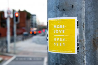Poster on lamp post that says more love less fear for post on insecurity