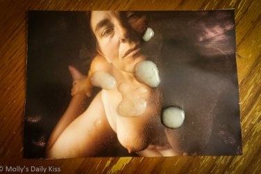 Photo of molly topless on a table with cum on the photo for post about cum tribute