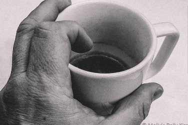 mans hand holding cup of coffee for a post about being fisted