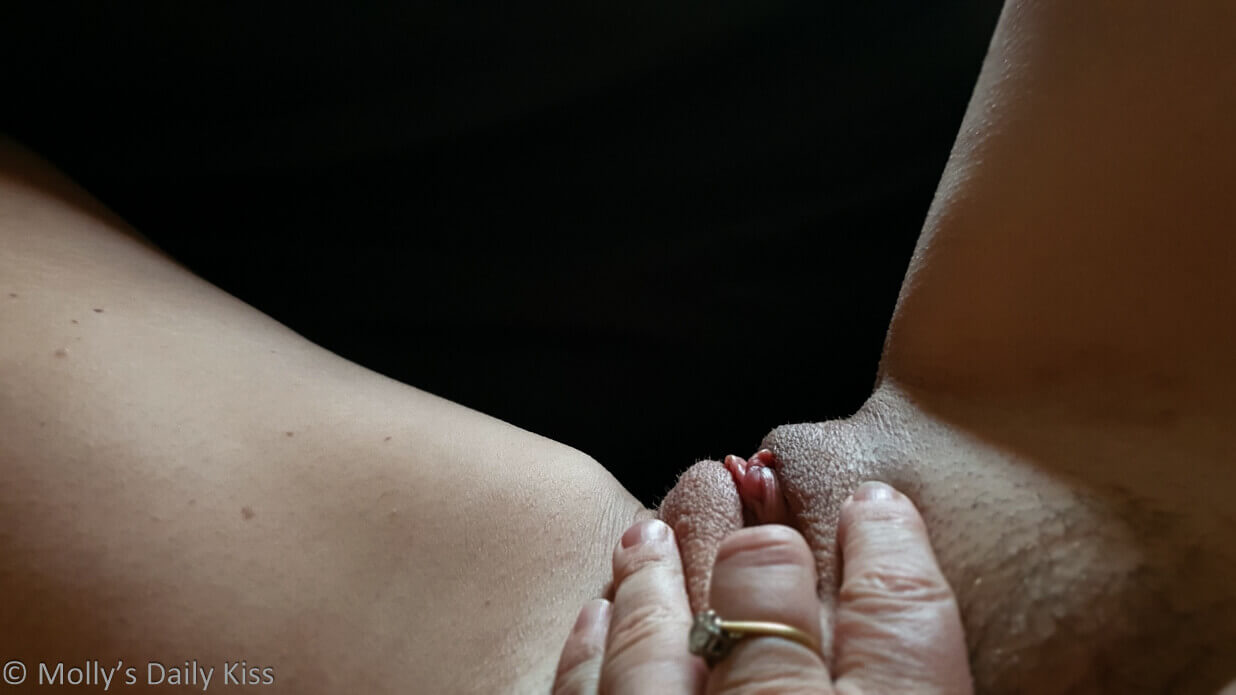 Molly with her legs open and her fingers touching her clit