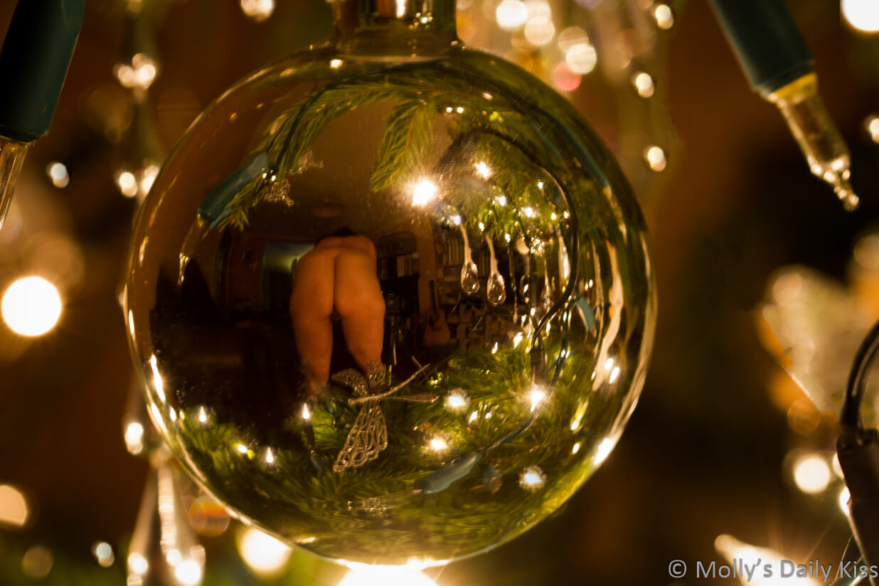 A view of molly bending over naked reflected in christmas bauble