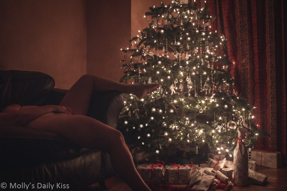 woman laying on sofa naked masturbating in front of christmas tree