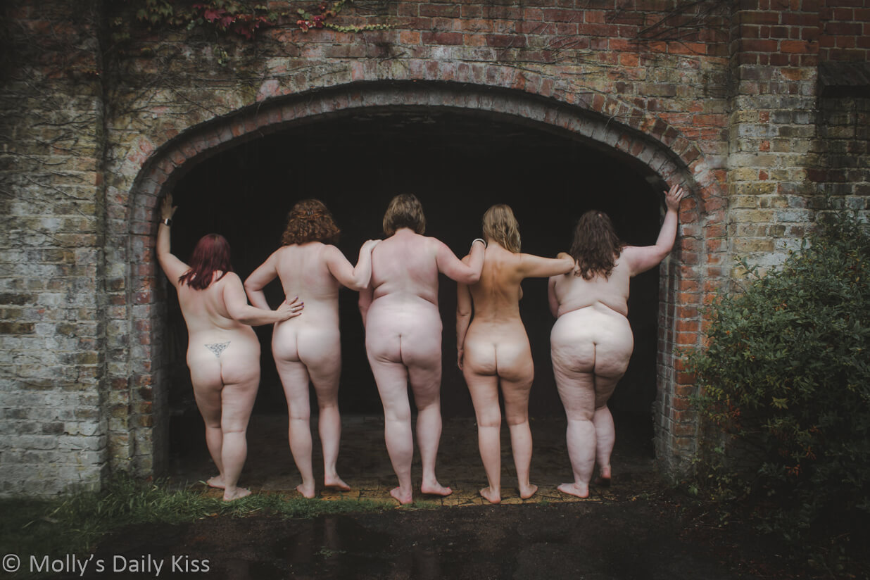 five naked women with back to camera in old archway for post about galentines
