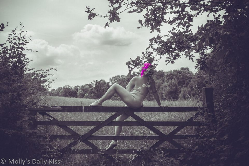 Molly sitting naked on a gate wearing pink head scarf