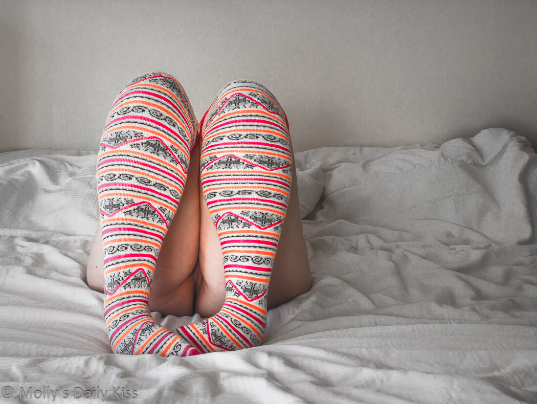 Molly laying on bed with knees bent so you can see her pussy between her thighs wearing pink pattern long socks