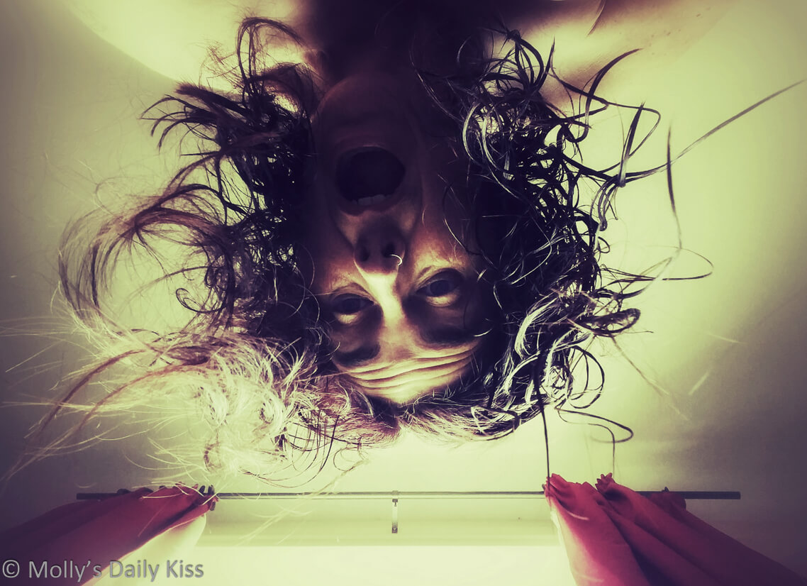 Molly looking down over camera with her hair falling round her like Medusa snakes and her mouth open in a scream