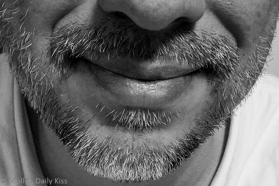Mans mouth and chin with beard in black and white