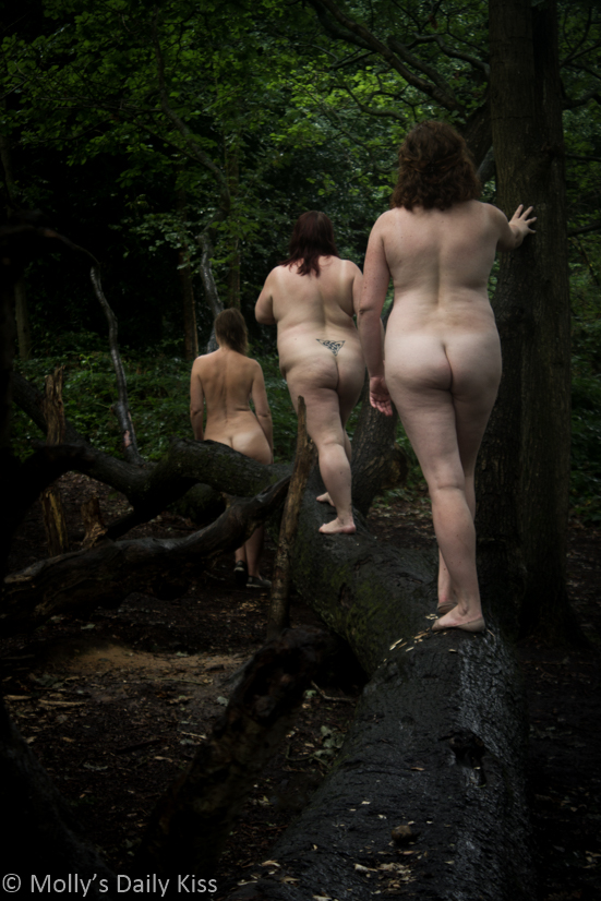 Three naked women lined up along a falled down tree
