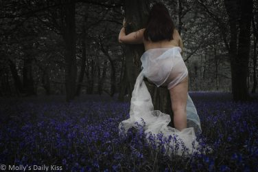 Molly wrapped in white tulle in bluebell woodlands