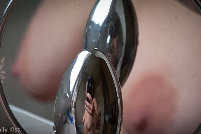 cropped image of molly's boobs in mirror with butt plug in front