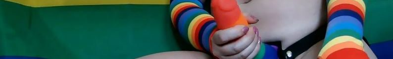 woman topless wearing pride sock and dildo in strap on