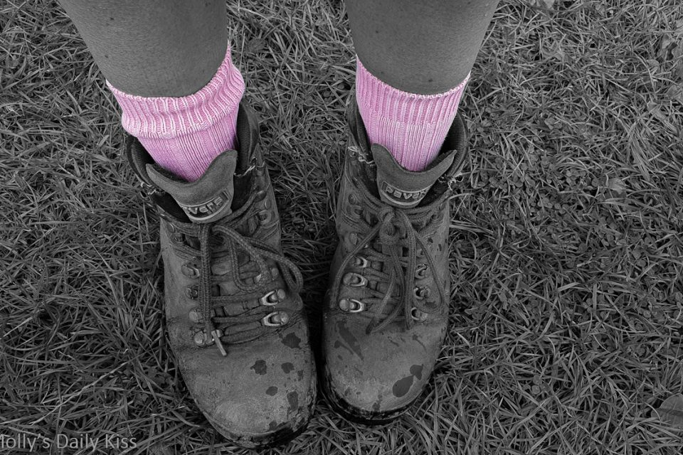 Black and white of molly wearing walking boots and bright pink socks in colour for post about exercise