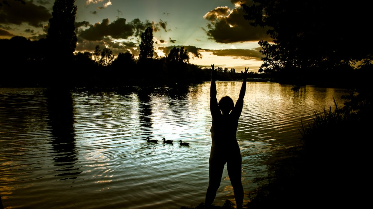 Molly standing naked in front of lake at sunset with 3 ducks on the water for post called Earth's Eye