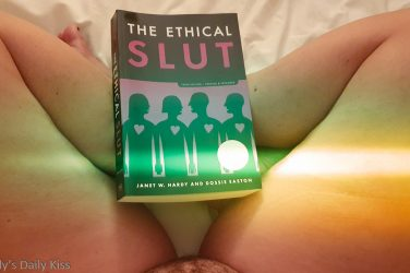 Molly sitting naked with copy of ethical slut on her lap for post about non monogamy and jealousy
