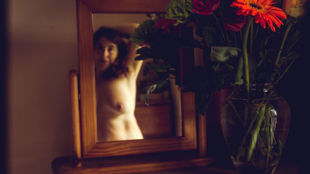 Molly topless in mirror with bunch of flowers in the vase next to the mirror