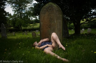 Molly laying at the foot of a gravestone masturbating for post about fucking in a graveyard