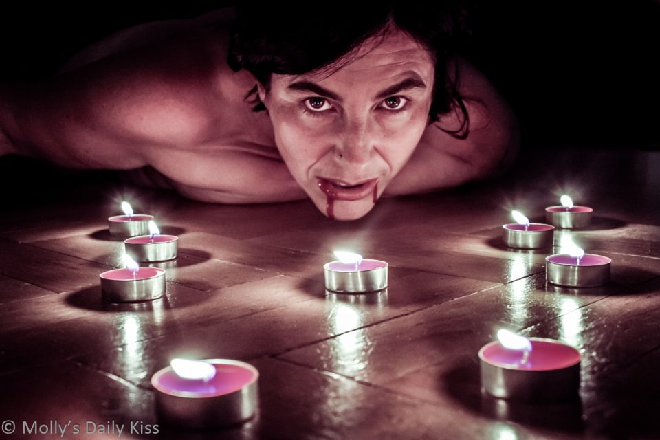 Molly laying on the floor in circle of candles with blond on her lips and chin