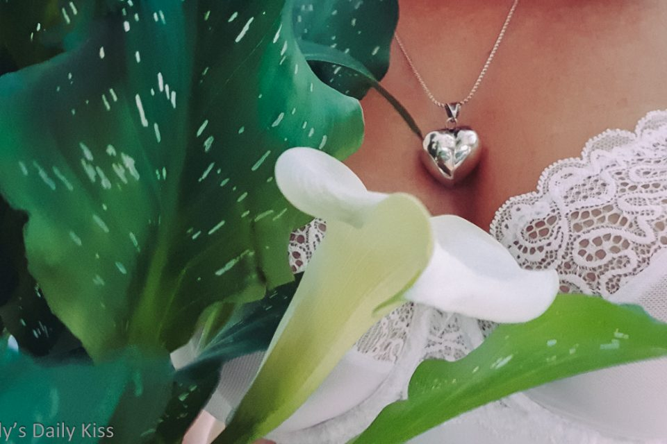 White cala lilly against Molly wearing white bra and heart shaped locket