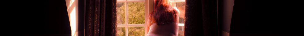 Molyl leaning out of window with sunlight on her hair and thigh dreaming of better time