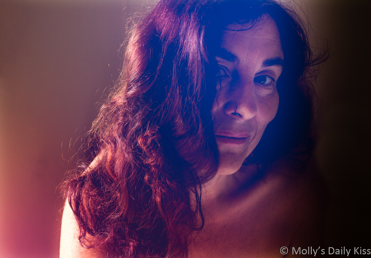 Molly looking in a flirting way at the camera with a red light falling across her curly hair