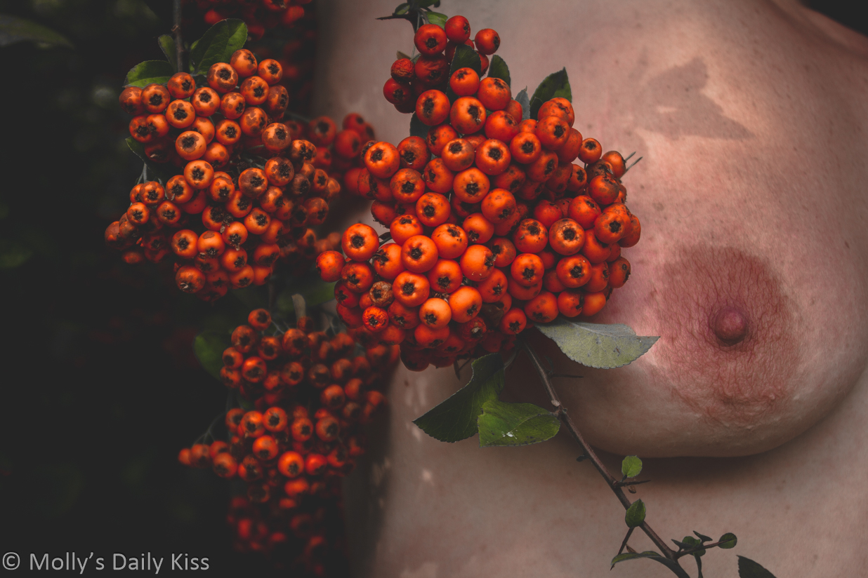 Coral beads of hawthorn in front of Molly's breast