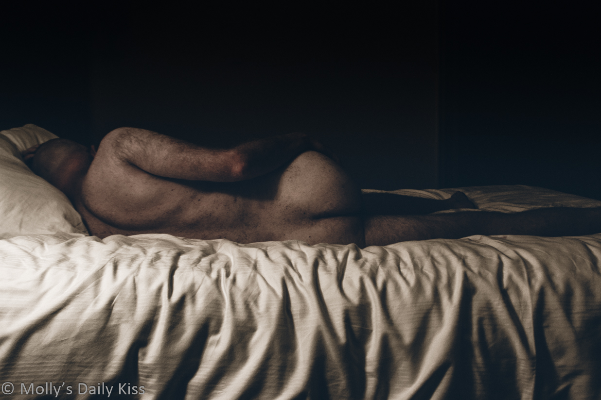 image of mollys lover with his back to the camera laying on the bed captures the essence of him