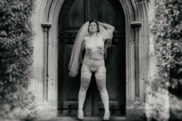 cropped image of molly standing in church doorway in bridal lingerie