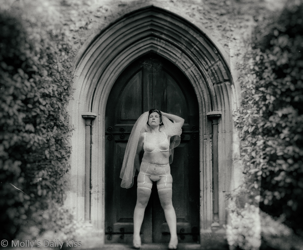 molly in white bridal lingerie and bridal veil in doorway of church