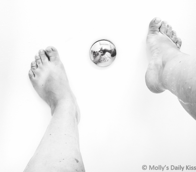 naked molly reflected in bath plug